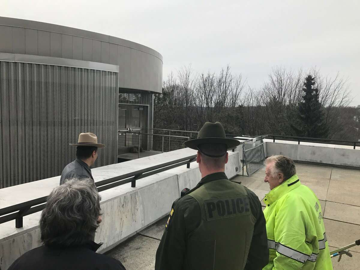 The state Department of Environmental Conservation and State Police investigate a coyote on the roof of the State Museum in Albany on Tuesday, March 27, 2018. (NYSDEC)