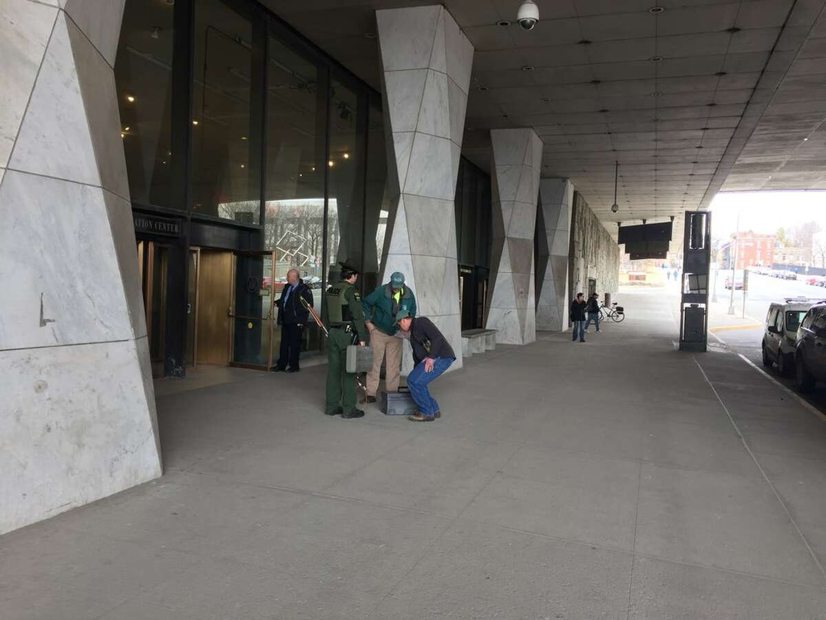 State Police, an animal control officer and DEC personnel with dog control gear attempt to capture a coyote at the state library on Tuesday, March 27, 2018, in Albany, NY. (Rick Karlin/Times Union)
