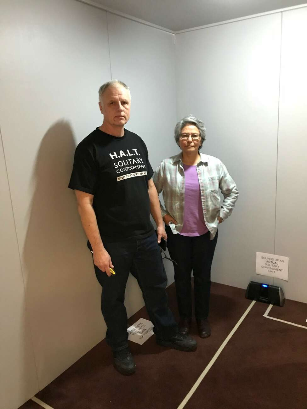 Alicia Barraza, left, and her husband, Douglas Van Zandt, inside a replica solitary confinement cell set up on Sunday, March 18 at Siena College for a performance of
