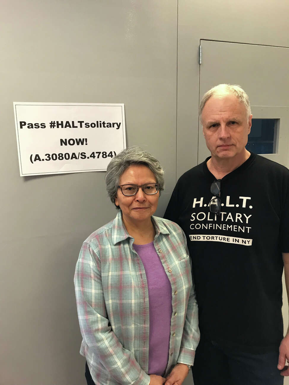 Alicia Barraza, left, and her husband, Douglas Van Zandt, in front of a replica solitary confinement prison cell he built to urge prison cell after his 21-year-old son Ben hung himself in a solitary cell