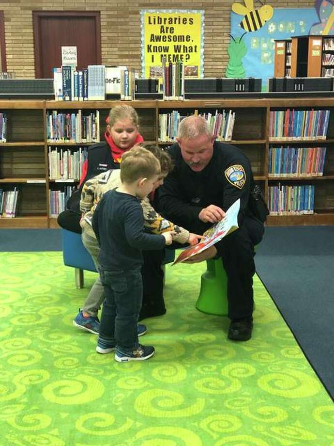 Police officers surely have plenty of stories, but it was a different kind of story time last Thursday at the Wood River Public Library. Wood River police officer Chris Alfaro read stories to children at the library. Thanks to funds provided by the Mustache March 4PD, Alfaro was also able to give each child an Easter egg full of candy.