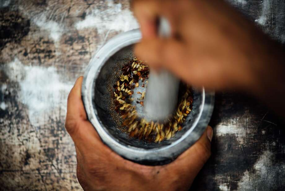 Use a mortar and pestle or spice grinder to grind fennel seeds, peppercorns and chile flakes into a fine powder for spiced Easter fruit salad. Photo: Nik Sharma