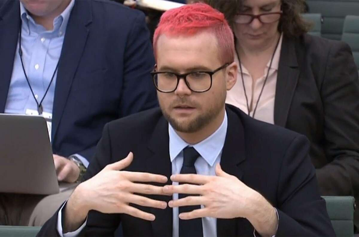 """A video grab from footage broadcast by the UK Parliament's Parliamentary Recording Unit (PRU) shows Canadian data analytics expert Christopher Wylie who worked at Cambridge Analytica appears as a witness before the Digital, Culture, Media and Sport Committee of members of the British parliament at the Houses of Parliament in central London on March 27, 2018 as part of the committee's investigation into fake news. Cambridge Analytica, which worked on US President Donald Trump's election campaign, has been accused of illegally mining tens of millions of users' Facebook data and using it to target potential voters. Christopher Wylie, a 28-year-old Canadian data analytics expert who worked with Cambridge Analytica and Kogan, blew the whistle on the scandal by revealing that more than 50 million Facebook profiles had been accessed without approval. / AFP PHOTO / PRU AND AFP PHOTO / PRU / RESTRICTED TO EDITORIAL USE - MANDATORY CREDIT """" AFP PHOTO / PRU """" - NO USE FOR ENTERTAINMENT, SATIRICAL, MARKETING OR ADVERTISING CAMPAIGNSPRU/AFP/Getty Images"""
