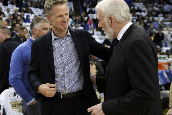 Head coaches Steve Kerr and Gregg Popovich chat before the Golden State Warriors played the San Antonio Spurs at Oracle Arena in Oakland, Calif., on Thursday, March 8, 2018.