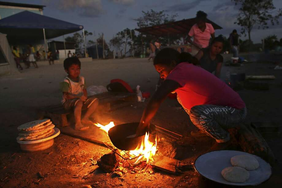 A Warao woman cooks at a camp in Pacaraima, Brazil, where many indigenous people have fled from Venezuela political crisis. Photo: Eraldo Peres, Associated Press