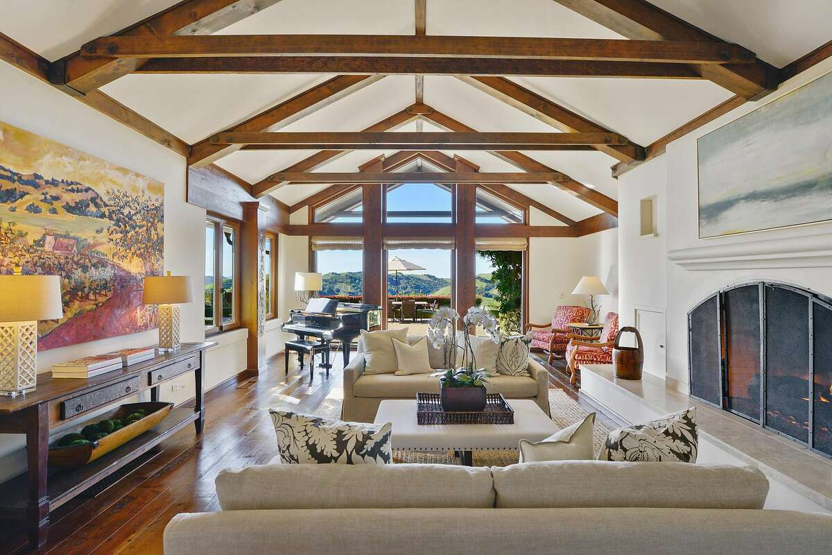 The living room at the five-bedroom Orinda home features a vaulted, beamed ceiling and a baronial fireplace.