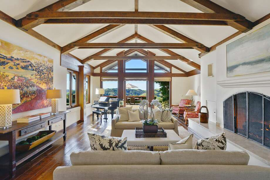 The living room at the five-bedroom Orinda home features a vaulted, beamed ceiling and a baronial fireplace. Photo: Open Homes Photography