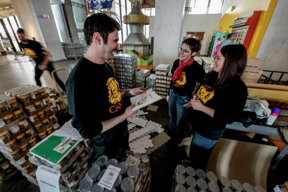Members of the CS Arch firm surrounded by boxes of canned food start their can build at the New York State Museum Tuesday March 27, 2018 in Albany, N.Y. Members of the team from left to right are; Brendan Brogan, design builder;  Caitlin Daly, architect and Erin Fisher Root, marketing.  Local architecture, engineering and construction teams build Bon Voyage-themed canned good structures to benefit local food pantries.  CanStruction exhibit opens to the public Wednesday.