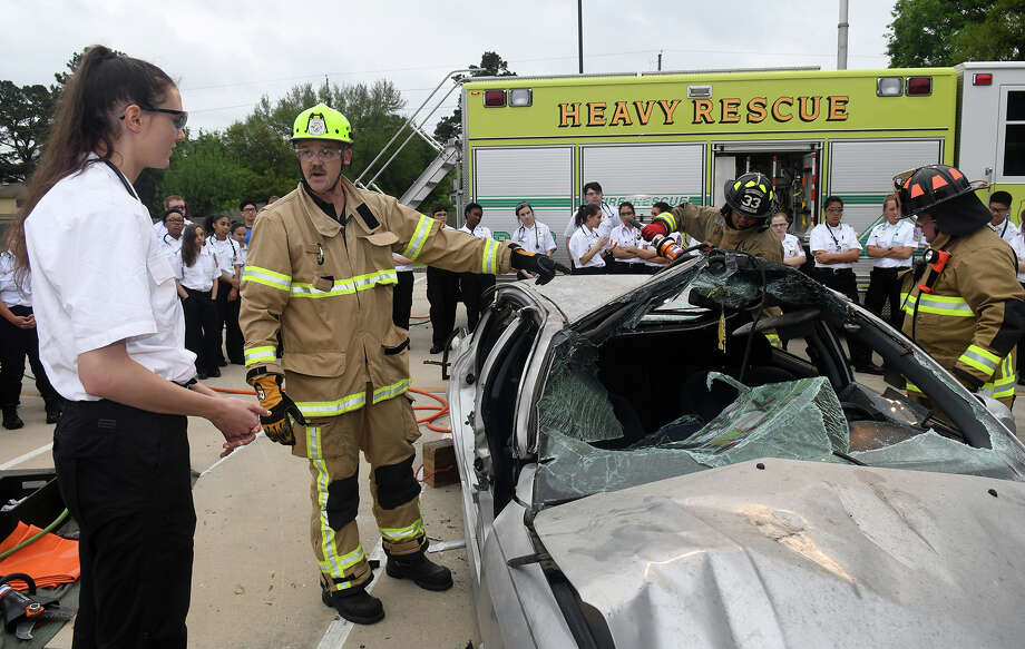 "Maggie Stephenson, 17, from left, a Klein High School senior, with her fellow EMT students from the Spring, Klein, and Tomball school districts, gets a close-up look at car wreck extrication from Klein Fire Dept. and Rescue member William Manning, with help from his team, including Mike Herrera and Carson McMath, as they lead the instruction during ""Extrication Day"" held in the Cypress Creek EMS parking lot and coordinated by Cypress Creek EMS as part of the student's EMT training. (Photo byy Jerry Baker/Freelance) Photo: Jerry Baker, Freelance / Freelance"
