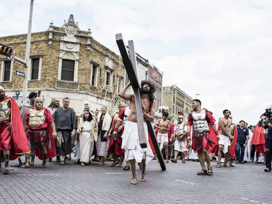 Luis Amaro, an actor playing Jesus, carries the cross during the San Fernando Cathedral passion play on Good Friday in downtown San Antonio last year. Photo: Matthew Busch /For The San Antonio Express-News / © Matthew Busch