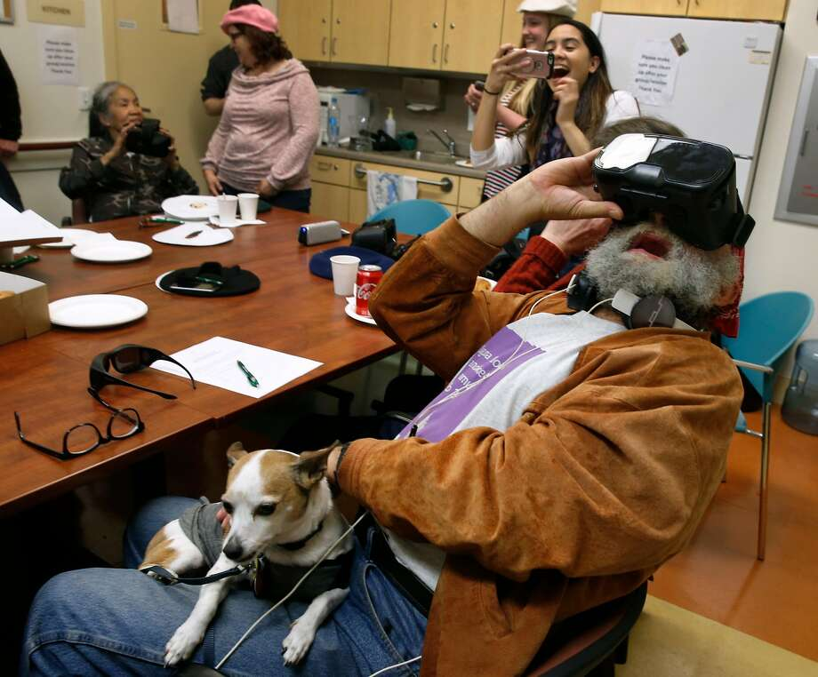 With his dog, Mister, on his lap, CJ Peoples experiences a VR roller coaster while trying virtual reality glasses for the first time at the Curry Senior Center in San Francisco. Photo: Paul Chinn / The Chronicle