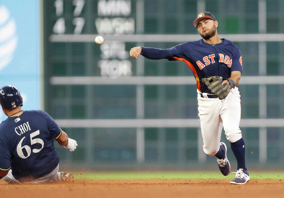 Houston Astros Jack Mayfield tries to make the throw to first after tagging Milwaukee Brewers first baseman Ji-Man Choi (65) out during the seventh inning of an MLB exhibition game at Minute Maid Park, Tuesday, March 27, 2018, in Houston.