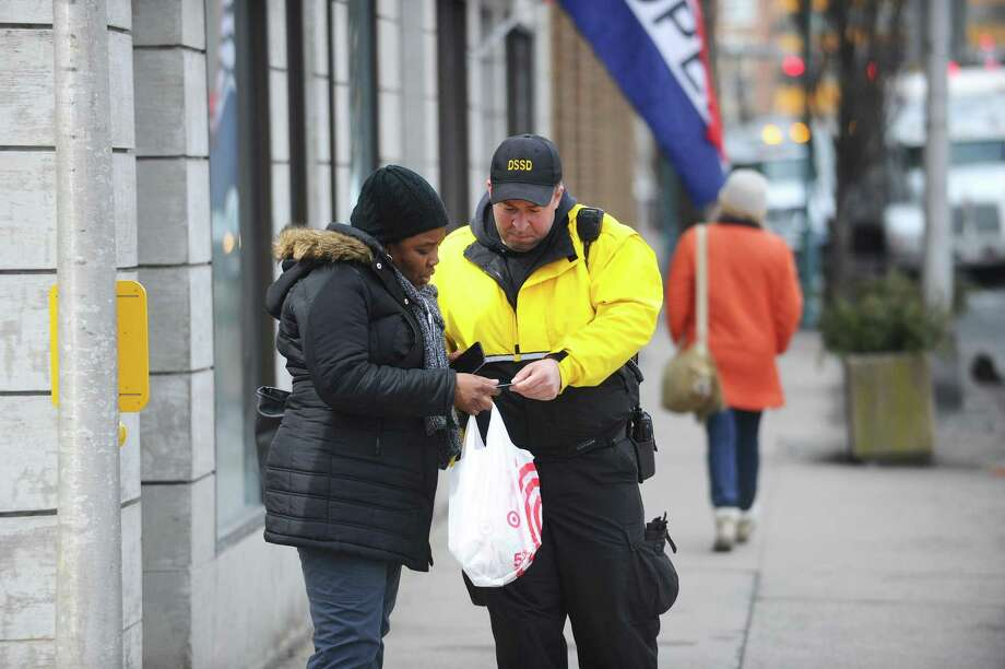 Stamford Downtown ambassador Brian Leahy hands Julieann Walker a $10 grocery store coupon after she properly crossed the intersection of Broad St. and Summer St. in downtown Stamford, Conn. on Tuesday, March 27, 2018. Photo: Michael Cummo / Hearst Connecticut Media / Stamford Advocate