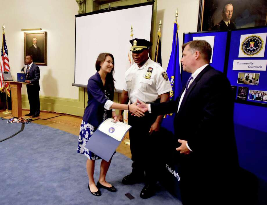 Charles K. Grady, FBI community outreach specialist, left, and Yale Police Chief Ronnell Higgins, center, who worked together establishing the Future Law Enforcement Youth Academy between Yale University and the FBI, with Kevin James Kline, assistant FBIspecial agent in charge in New Haven, far right, congratulate FLEYA graduate Lauren Low of Hamden, 17, and 25 other teens in the FLEYA program in 2016 at Yale's Woolsey Hall Presidents Room. FLEYA is the nation's first week-long overnight academy hosted by the FBI and an Ivy League university. The FLEYA program is developed as a selective and intense education program for Connecticut youth who wish to pursue careers in law enforcement. FLEYA offers academic and practical classes set in a college environment that includes instruction from the FBI, Yale Police, various Connecticut law enforcement personnel, the U.S. Attorney Office, and academic experts in forensics. Photo: Peter Hvizdak / Hearst Connecticut Media File Photo / ©2016 Peter Hvizdak