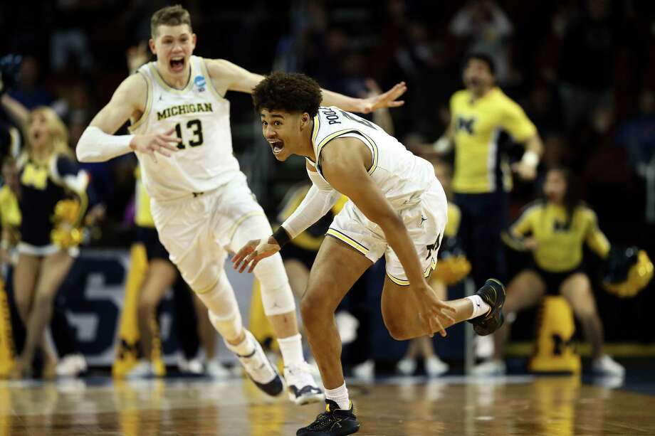 WICHITA, KS - MARCH 17:  Jordan Poole #2 and Moritz Wagner #13 of the Michigan Wolverines celebrate Poole's 3-point buzzer beater for a 64-63 win over the Houston Cougars during the second round of the 2018 NCAA Men's Basketball Tournament at INTRUST Bank Arena on March 17, 2018 in Wichita, Kansas.  (Photo by Jamie Squire/Getty Images) Photo: Jamie Squire, Staff / Getty Images / 2018 Getty Images