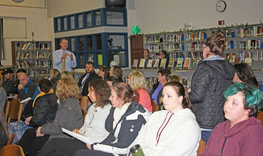 (Left) Bad Axe High School principal Kurt Dennis addresses a parent's question at Monday's school board meeting regarding the administration's pitch to realign the district. More than 20 parents packed into the high school library to hear the proposal, voice their concerns and ask questions. The board may vote on the proposal at the April 23 meeting. Photo: Bradley Massman/Huron Daily Tribune