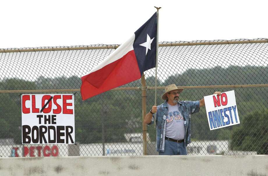 A protester waves a Texas flag and anti-immigration signs during a 2014 protest against illegally immigrants in Conroe, Texas. Photo: Jason Fochtman, Photographer / AP