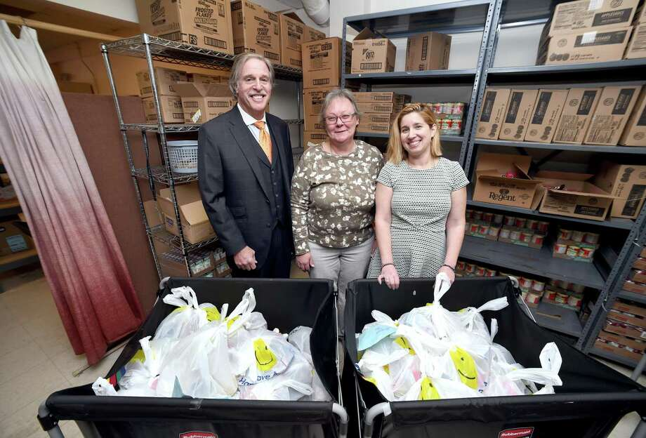 Left to right, Richard Epstein, president of C.H. Brenner Insurance, Sandy Hagan, director of the food pantry, and Rachel Scolnic Dobin, program director for Jewish Family Service, are photographed behind bags of food in the Food4Kids program at the Food Pantry and Nutritional Health Center in New Haven on March 27, 2018.  Food4Kids has received a large donation from the Safeco Insurance Company. Photo: Arnold Gold / Hearst Connecticut Media / New Haven Register