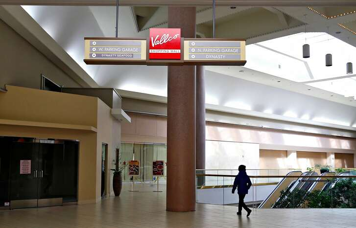 A woman walks through the Vallco shopping mall in Cupertino, Calif. on Wednesday, Feb. 14, 2018. Few tenants remain at the mall in the western Santa Clara Valley, including an AMC Theater and a couple of restaurants, but it is largely abandoned.