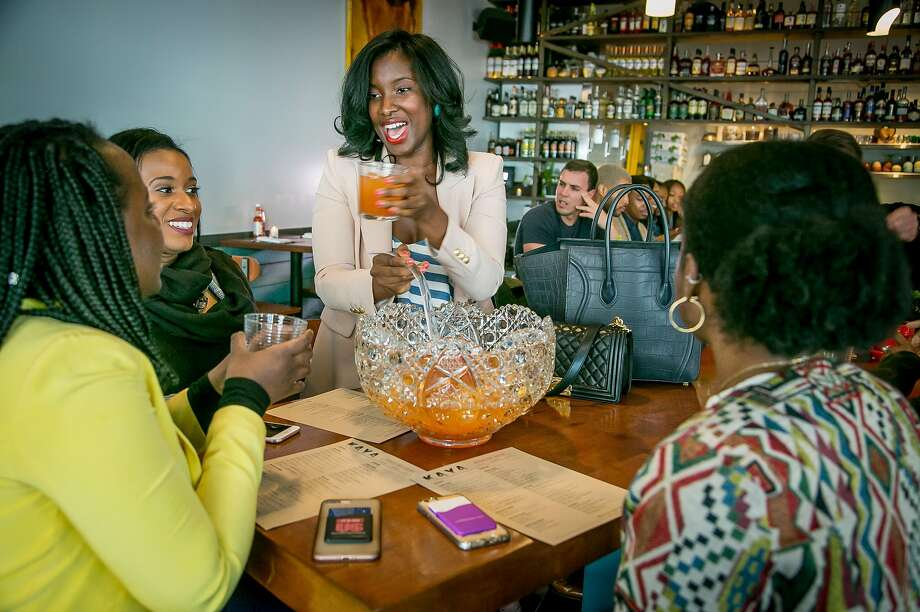 Diner Safiya Jihan (center) pours drinks from a punch bowl for her friends at Kaya restaurant in S.F. Photo: John Storey / Special To The Chronicle