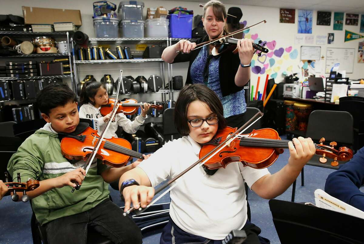( l to r ) Daniel Valdizon, Yareli Perez and Jason Carvalho under the guidance of Sarah Moulder as she leads her 6th grade string orchestra students at Ravenswood Middle School in East Palo Alto, Calif. as seen on Tues. Mar. 27, 2018.