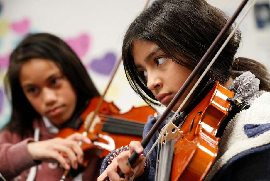 Keila Ambriz (right) plays violin in Sarah Moulder's sixth-grade orchestra class at Ravenswood Middle School. Photo: Michael Macor / The Chronicle
