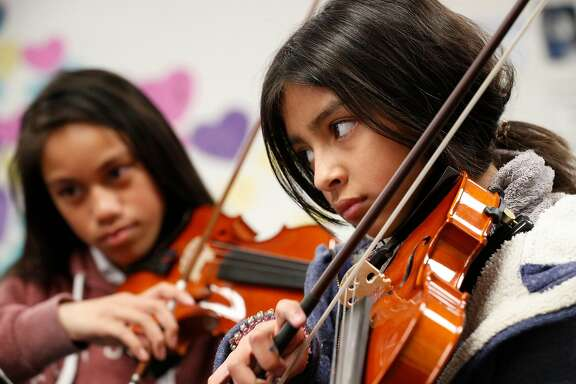 Keila Ambriz, (right) on violin in Sarah Moulder's 6th grade string orchestra class at Ravenswood Middle School in East Palo Alto, Calif. as seen on Tues. Mar. 27, 2018.