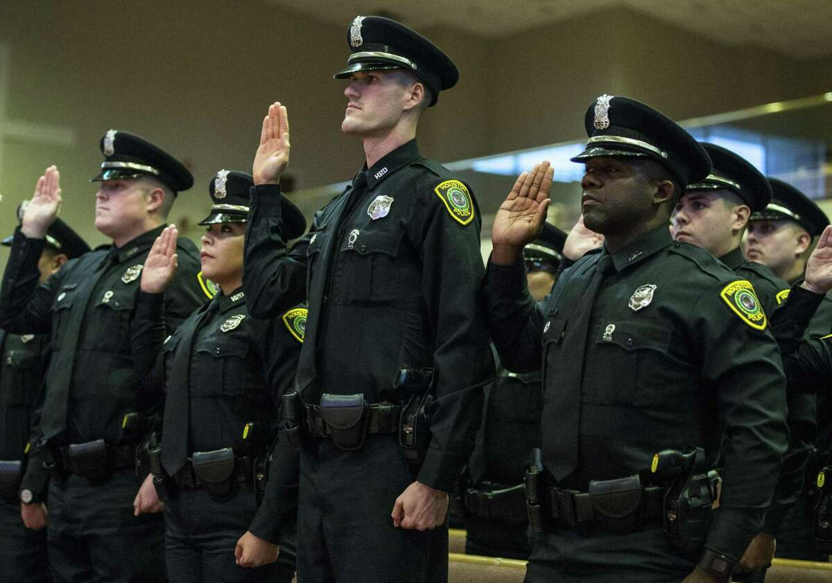 New Houston police officers are sworn in during the graduation ceremony of HPD Cadet Class 232 at Greater Grace Outreach Church in Houston on Oct. 2, 2017.