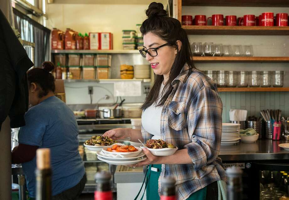 Reyna Aguirre runs an order from the kitchen to a table at Homeroom restaurant in Oakland. Photo: Jessica Christian / The Chronicle