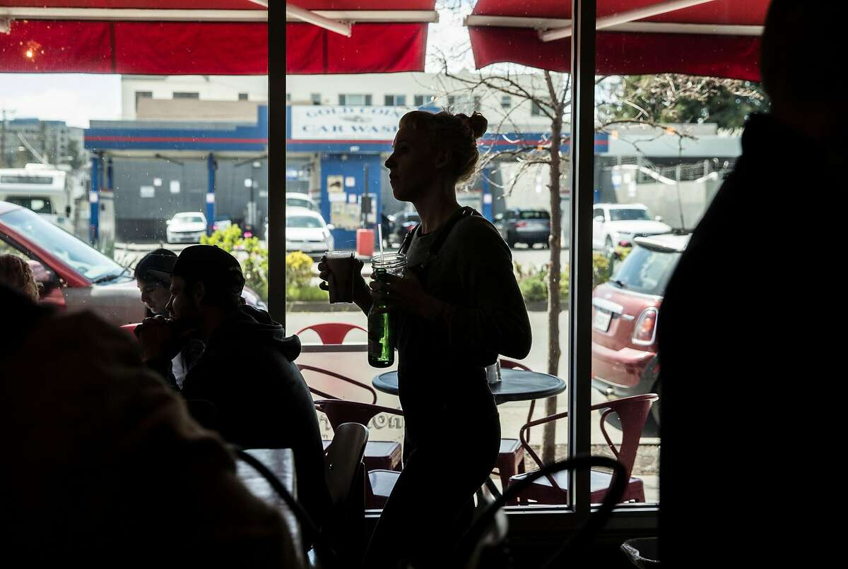 Julie Snook runs a drink to a customer at Homeroom restaurant Friday, March 23, 2018 in Oakland, Calif.