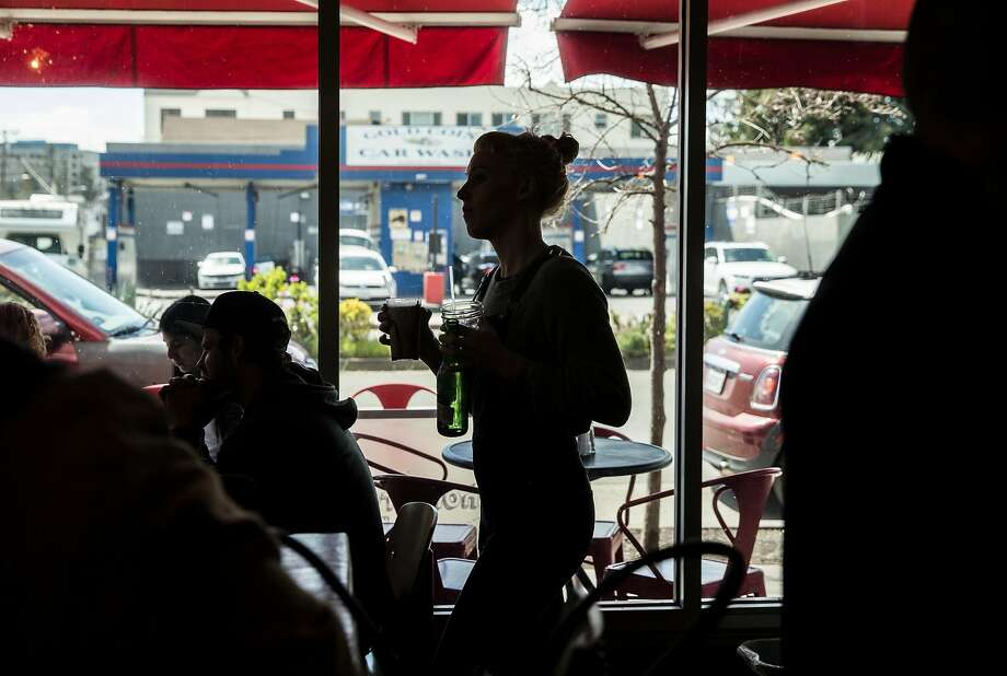 Julie Snook runs a drink to a customer at Homeroom restaurant in Oakland. Photo: Jessica Christian / The Chronicle