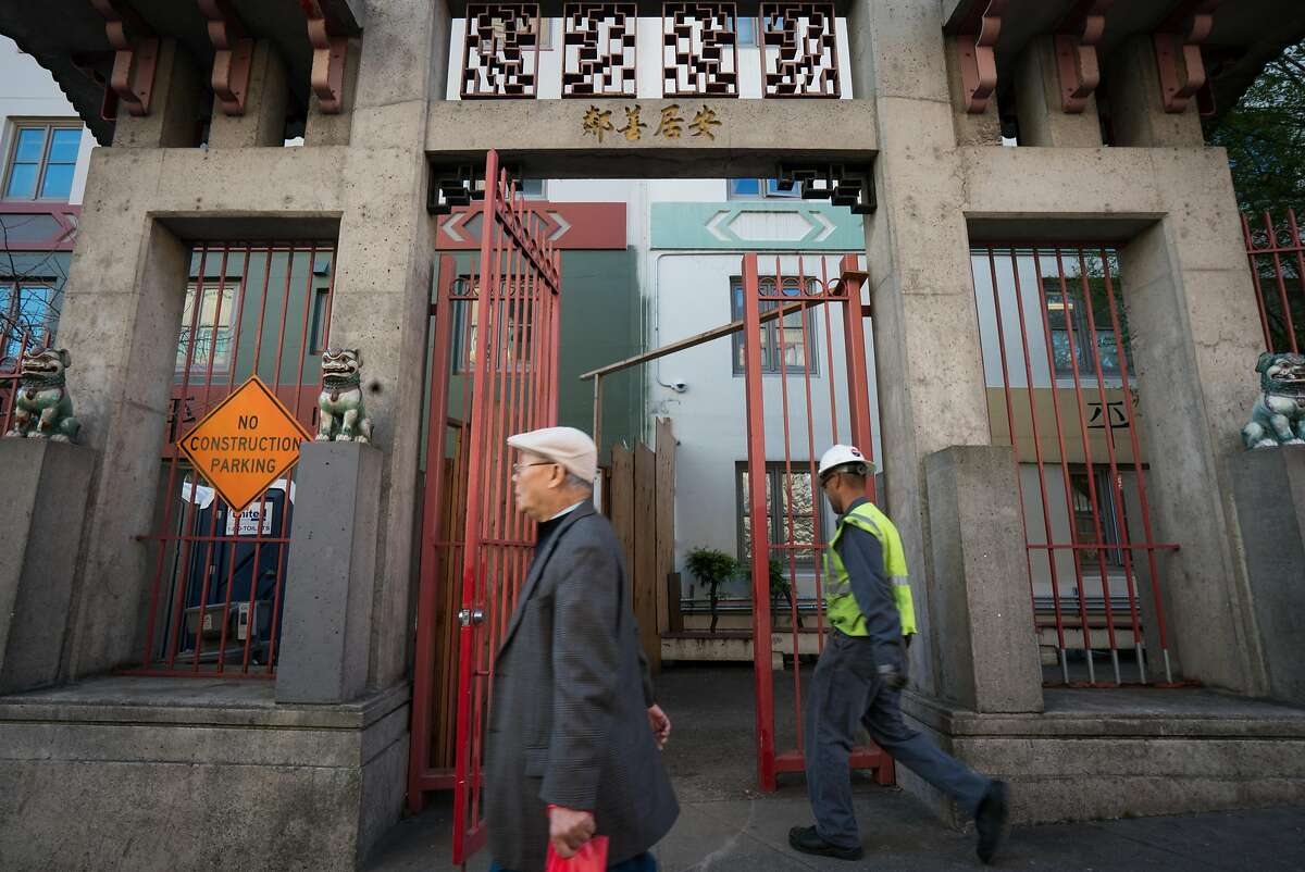 People walk past construction at the Ping Yuen housing development building in Chinatown in San Francisco, Calif. on Tuesday, March 27, 2018.
