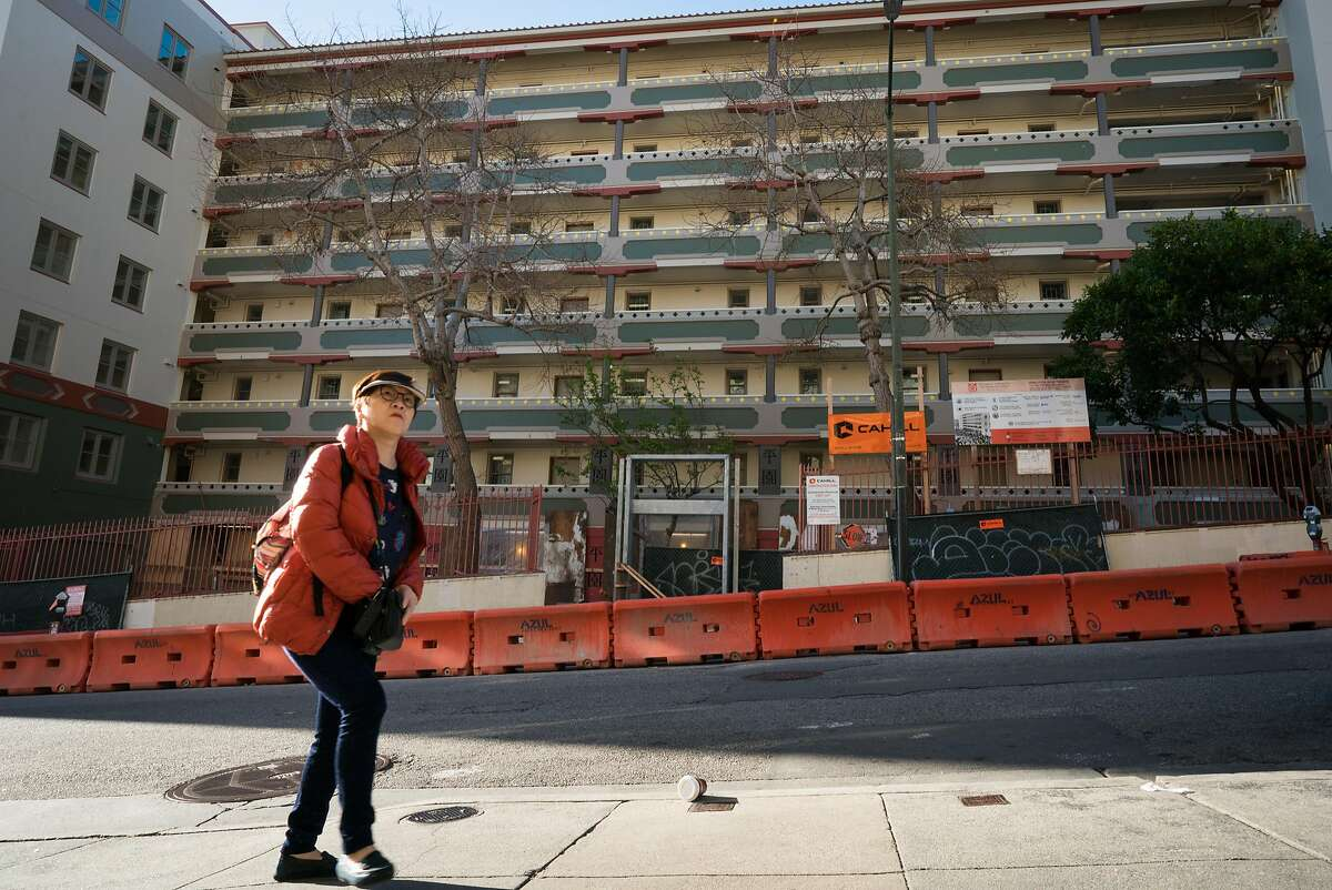 A woman walks past construction in Chinatown in San Francisco.