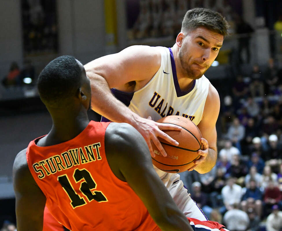 Former UAlbany basketball player Greig Stire, shown knocking over Stony Brook's Tyrell Sturdivant in Stire's final college game this month, is trying out for the Great Dane football team this spring. (Hans Pennink/Special to the Times Union)