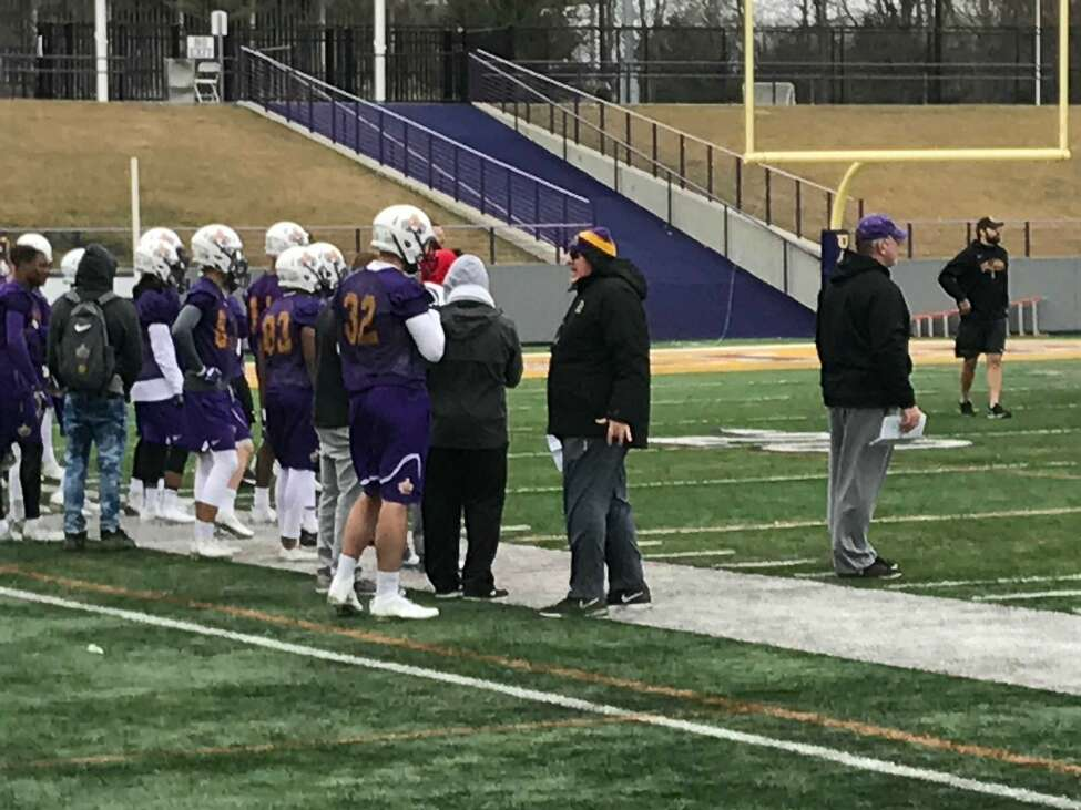 Former UAlbany basketball player Greig Stire (32), trying out for the football team, talks to head coach Greg Gattuso at practice today. (Mark Singelais/Times Union)
