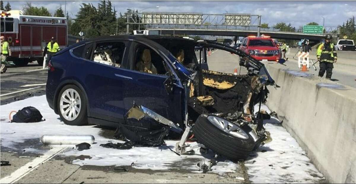 In this Friday March 23, 2018 photo provided by KTVU, emergency personnel work a the scene where a Tesla electric SUV crashed into a barrier on U.S. Highway 101 in Mountain View, Calif. The National Transportation Safety Board has sent two investigators to look into a fatal crash and fire Friday in California that involved a Tesla electric SUV. The agency says on Twitter that it's not clear whether the Tesla Model X was operating on its semi-autonomous control system called Autopilot at the time. Investigators will study the fire that broke out after the crash. (KTVU via AP)