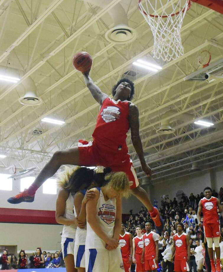 Kevin Porter jumps over three people on a dunk during the American Family Insurance Slam Dunk and 3-Point Championships at Wagner High School on Tuesday, March 27, 2018. The contest coincides with the NCAA Final Four in San Antonio. Photo: Billy Calzada, Staff / San Antonio Express-News / San Antonio Express-News