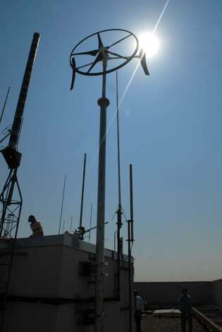 A windmill, part of a pilot project, sits atop the Corning Tower in Albany.  In cost-cutting and energy-saving move, OGS is turning down the hours of A/C operation and turning up the themostats as temperatures are rising in state offices this summer.  (Paul Buckowski / Times Union) Photo: PAUL BUCKOWSKI / 00008903A