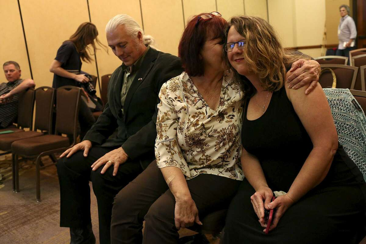 Sherri Pomeroy is embraced by her sister, Sylvia Timmons, at the conclusion of the press conference announcing the new building plans for First Baptist Church of Sutherland Springs at the Hilton San Antonio Airport on Tuesday, March 27, 2018. At left is Mark Collins.