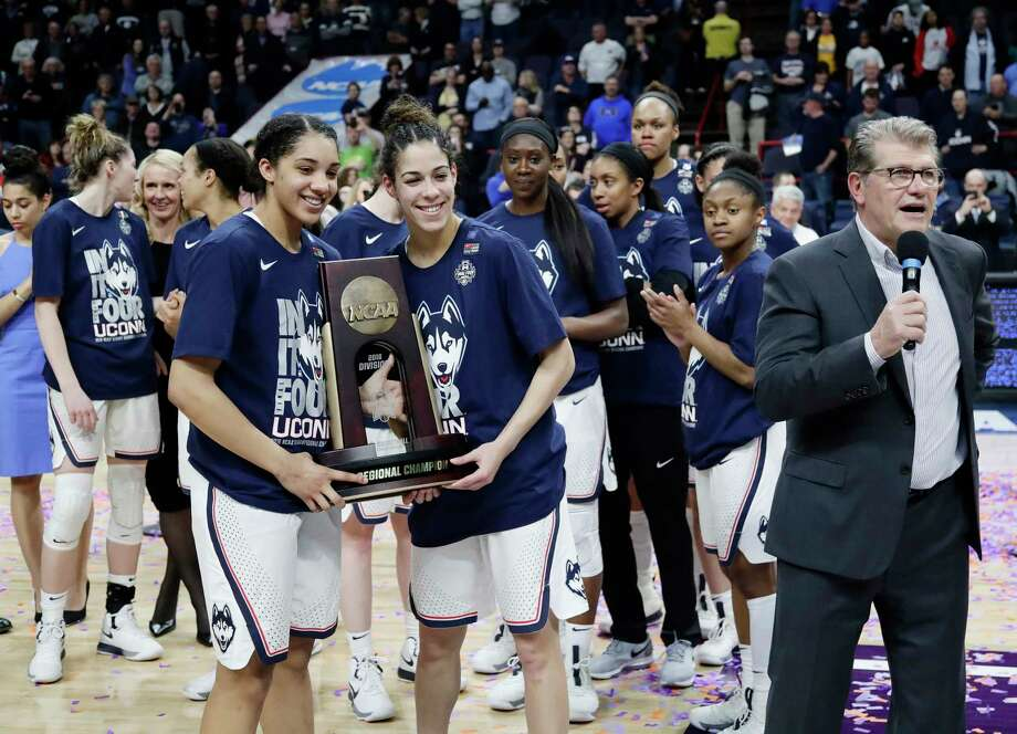 Connecticut's Gabby Williams, left, and Kia Nurse, center, hold the regional championship trophy as head coach Geno Auriemma, right, speaks after a regional final against South Carolina at the women's NCAA college basketball tournament Monday, March 26, 2018, in Albany, N.Y. (AP Photo/Frank Franklin II) Photo: Frank Franklin II / Copyright 2018 The Associated Press. All rights reserved.