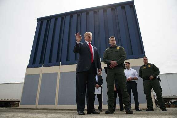 FILE - In this March 13, 2018 file photo, President Donald Trump talks with reporters as he reviews border wall prototypes in San Diego.  Trump is floating the idea of using the military�s budget to pay for his long-promised border wall with Mexico.  Trump raised the idea to House Speaker Paul Ryan at a meeting last week, according to a person familiar with the discussion who spoke on condition of anonymity. (AP Photo/Evan Vucci, File)