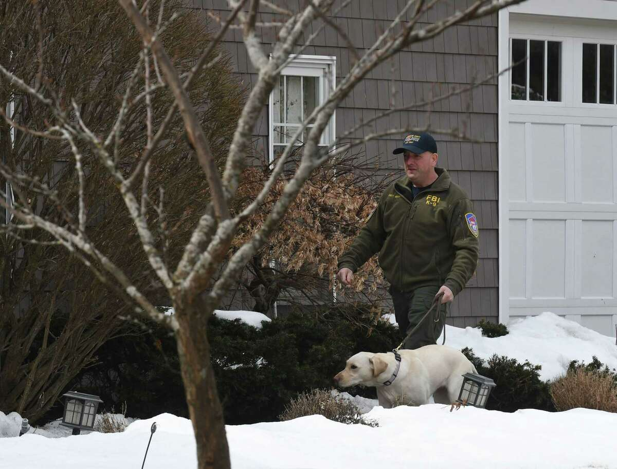 An FBI sniffer dog is brought to the home NXIVM co-founder Nancy Salzman which was raided by federal agents on Tuesday, March 27, 2018, in Halfmoon, N.Y. Keith Raniere, the co-founder of the NXIVM corporation has been arrested by the FBI based on a federal criminal complaint filed in the Eastern District of New York. (Will Waldron/Times Union)