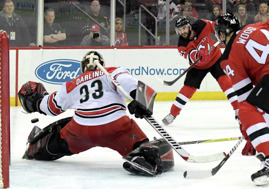New Jersey Devils right wing Kyle Palmieri (21) scores a goal past Carolina Hurricanes goaltender Scott Darling (33) during the second period of an NHL hockey game Tuesday, March 27, 2018, in Newark, N.J. The Devils won 4-3.(AP Photo/Bill Kostroun) Photo: Bill Kostroun / FR51951 AP