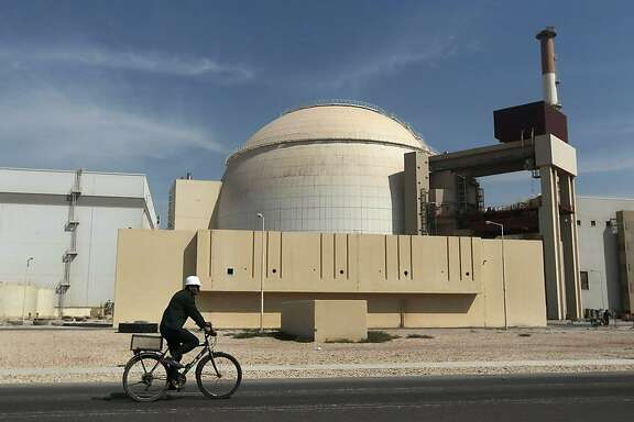 FILE - In this Oct. 26, 2010 file photo, a worker rides a bicycle in front of the reactor building of the Bushehr nuclear power plant, just outside the southern city of Bushehr. Iran and six world powers have agreed on how to implement a nuclear deal struck in November, with its terms starting from Jan. 20, officials announced Sunday. (AP Photo/Mehr News Agency, Majid Asgaripour, File)