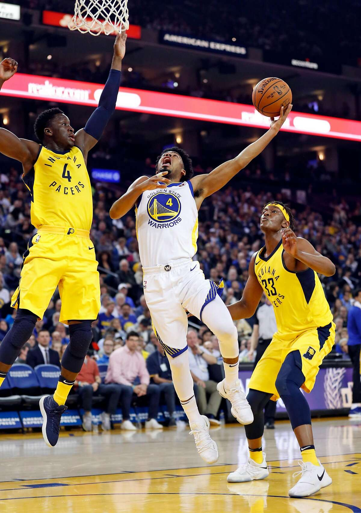 Golden State Warriors' Quinn Cook shoots between Indiana Pacers' Victor Oladipo (4) and Myles Turner in 2nd quarter during NBA game at Oracle Arena in Oakland, Calif., on Tuesday, March 27, 2018.