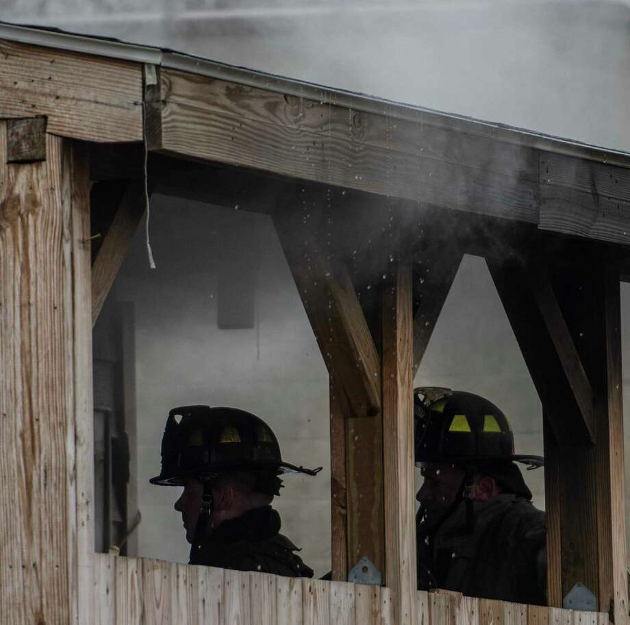 Fire fighters work on hot spots at a house fire at the corner of Glendale and 5th Avenue early Wednesday March 28, 2018 in Schenectady, N.Y.  A Vietnam veteran was rescued from the burning structure by City police after a civilian made an initial attempt to save the victim.  