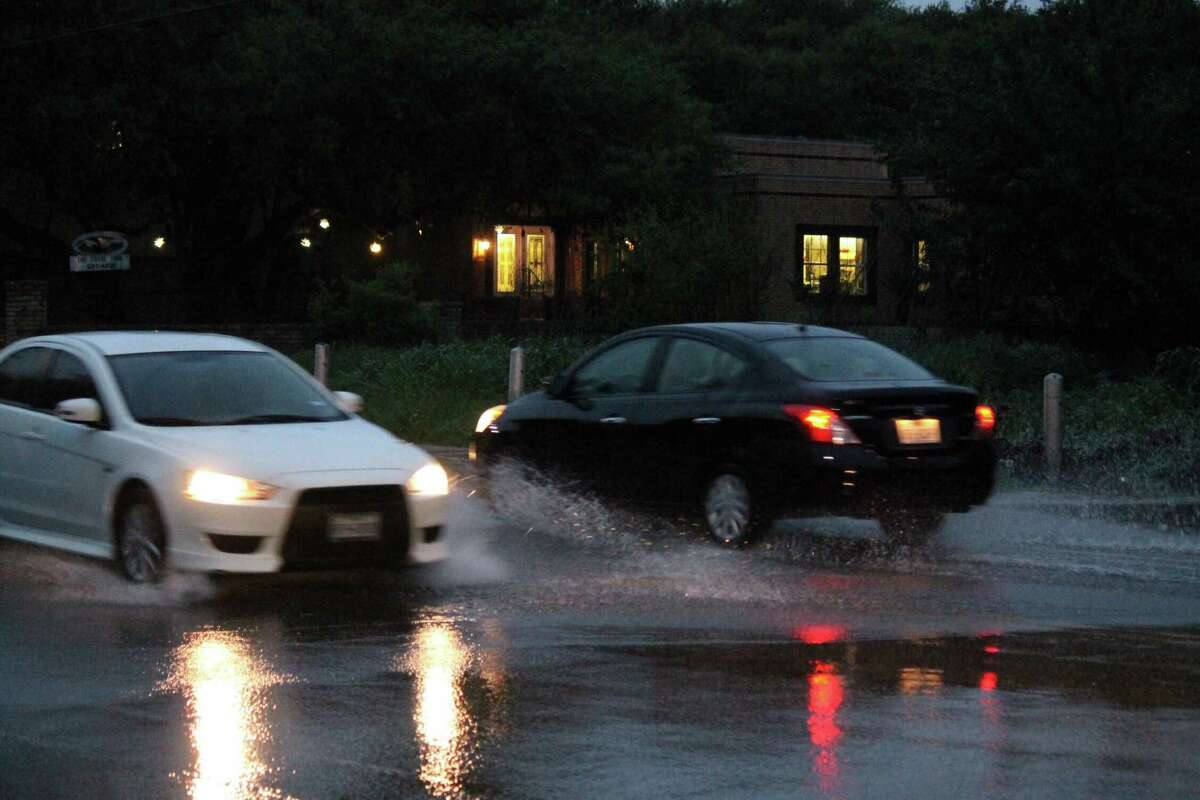 Cars zoom through standing water on Vance Jackson Road and Orsinger Lane on March 28, 2018.