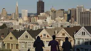 The silhouettes of pedestrians stand in front of Victorian homes and the downtown skyline in San Francisco, California.