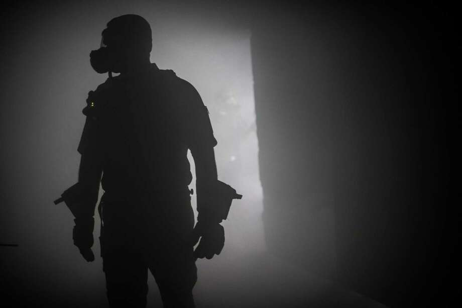 A member of the Houston Department stands inside a building filled with training smoke as part of the demonstrations about the process the firefighter have to go through to do their jobs effectively, Monday, Dec. 11, 2017, in Houston. ( Marie D. De Jesus / Houston Chronicle ) Photo: Marie D. De Jesus, Houston Chronicle / Houston Chronicle / © 2017 Houston Chronicle