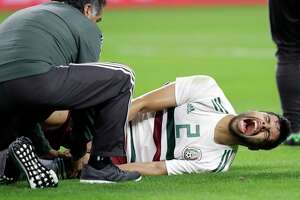 CORRECTS DATE OF PHOTO  - A member of the staff checks on Mexico defender Néstor Araujo (2) after Araujo suffered a leg injury in the first half of a friendly soccer match against Croatia in Arlington, Texas, Tuesday, March 27, 2018. (AP Photo/Tony Gutierrez)